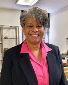 Photo of Pam Roberson standing in an office with dark blazer and pink collared shirty underneath
